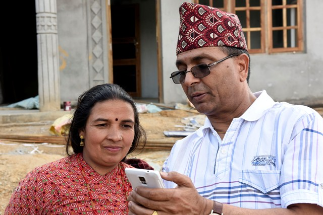 CEO Bhusal explaining a local woman the legal provisions of reconstruction.