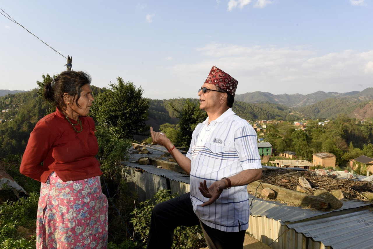 CEO Bhusal talking to Sabitri Humagain of Balthali-4 about the government provision to support single women like her to rebuild their houses.